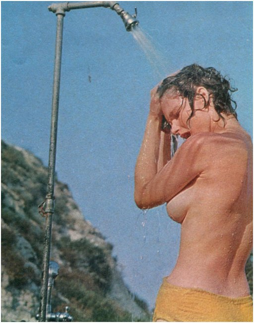 washing the sand out of her hair at a beach shower station