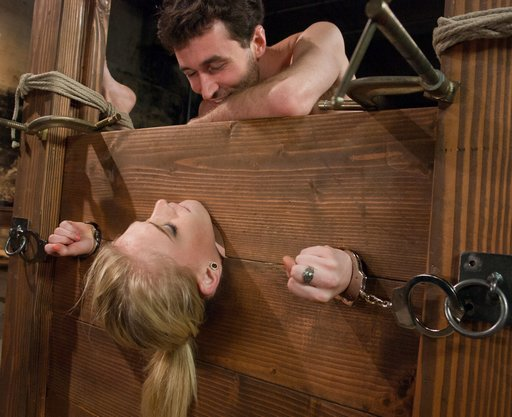 james deen checking in with allie james during bondage sex in a combination bondage stocks and bed