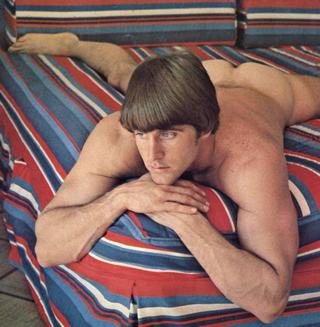 naked man on a long-out-of-style striped bedding set