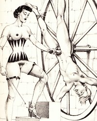 dominatrix masturbates man tied upside down on a bondage wheel