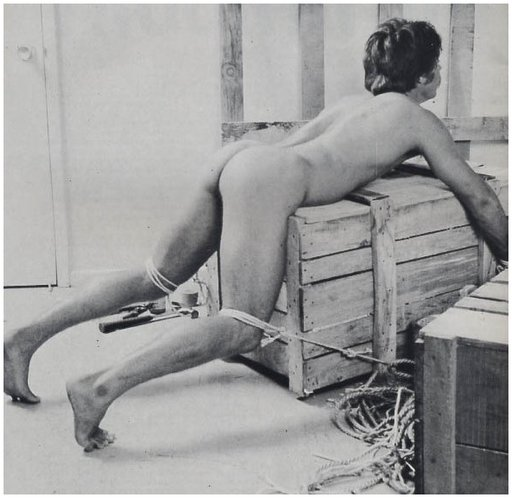 gay bondage; young man tied face down over a wooden crate
