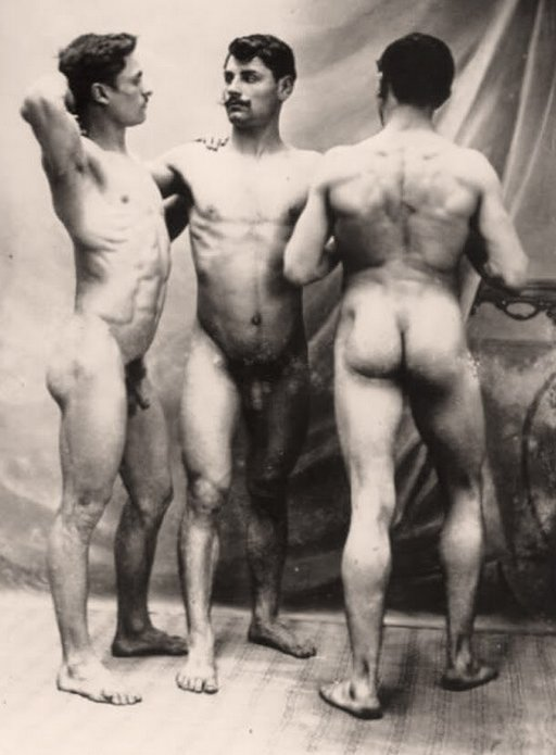 three buff naked men standing around admiring each other and their nude bodies