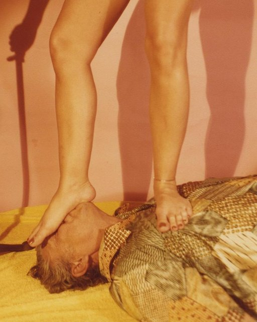 naked woman stepping on the face of an old man in silk pajamas