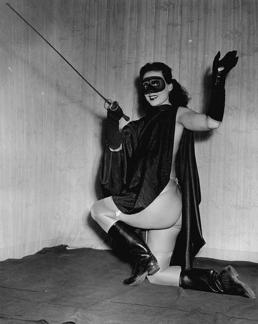 burlesque dancer in highwayman costume with mask and cape and sword and boots (and no pants)