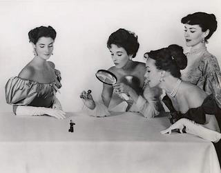four fine but cruel ladies examine tiny man under a magnifying glass and attempt to pierce him with a hat pin