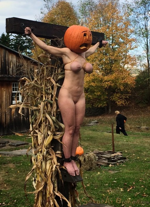 crucifixion of a bondage model with a pumpkin on her head posed as a scarecrow