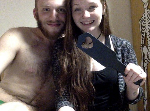 happy woman with a heart-cutout spanking paddle and a naked man cuddling her
