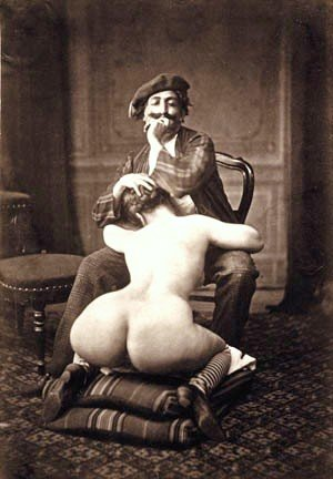 mustachioed man wearing a beret and sitting comfortably in a chair while getting a blowjob from a curvy woman who is kneeling before him on some cushions