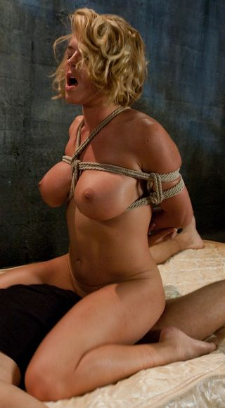 krissy lynn in rope bondage and kneeling astride a lucky man