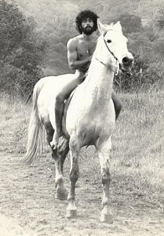 nude hippy man on a white horse
