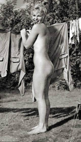 naked woman putting washing on the line