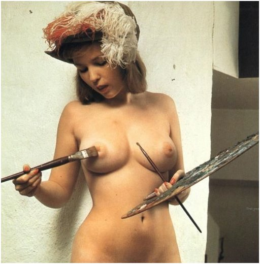 nude artist painting her nipple with a brush and painter's palette