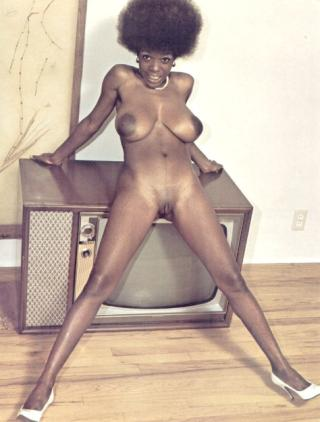 woman standing naked in front of an old console television