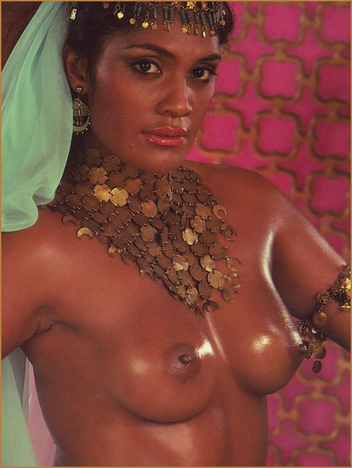 black woman with bare breasts, oiled skin, coin belt, and white scarf or veil
