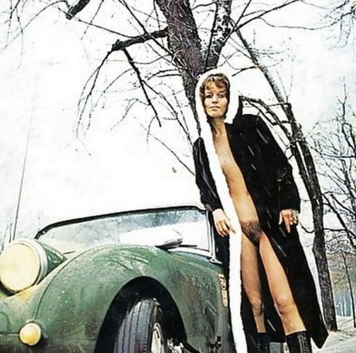 chilly porn star posing in fur coat by a fancy car in the snow