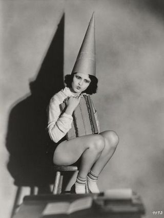 pretty girl wearing a dunce cap and looking puzzled