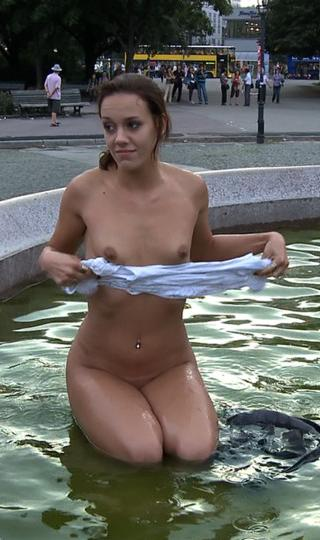 woman washes her clothes naked in a public fountain in Berlin