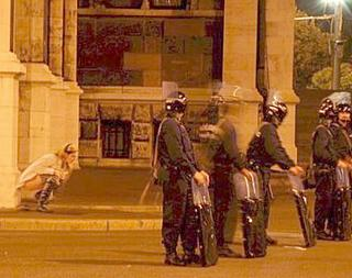 blonde woman squats to pee behind a line of riot police