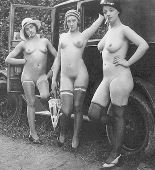 three cigarette-smoking whores/hookers/sex workers standing in lingerie next to a vintage automobile