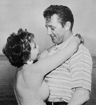 actor Robert Mitchum getting a hug from a topless woman