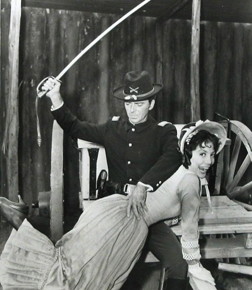 television promotional photo of a woman getting spanked with a cavalry sword