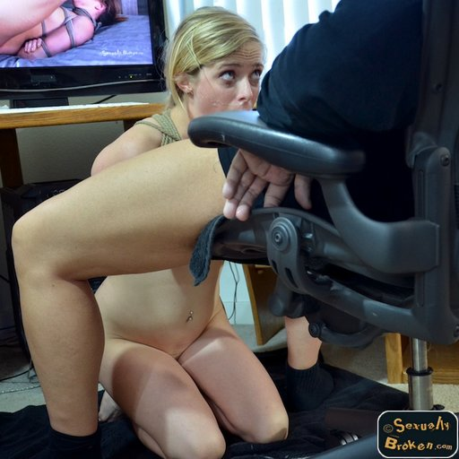 Penny Pax on her knees in bondage and preparing to service a man at his desk