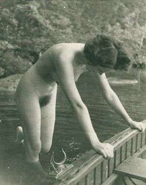 nude woman pushes boat out from shore