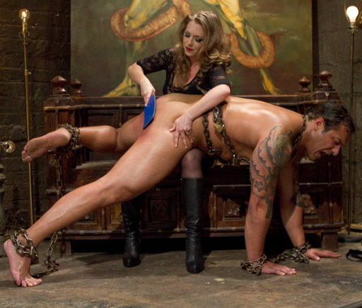 big huge man spanked and paddled hard over the knee of a much smaller dominatrix