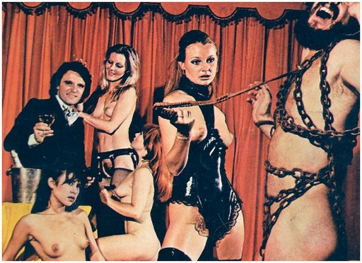 dominatrix performs femdom whipping on chained man while three simpering beauties pamper a dude with a bottle of champagne