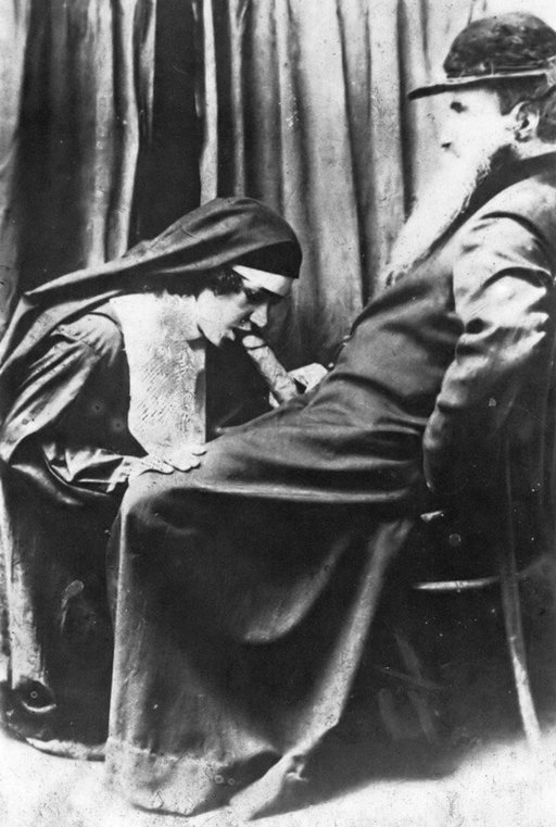vintage photo of a kneeling nun giving a blowjob to a comfortably seated bearded patriarch
