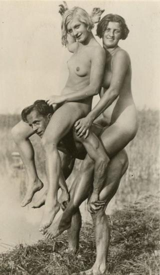 two naked woman riding horsey on one nude but very buff man