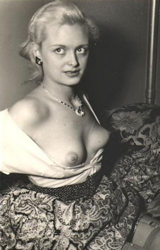 vintage topless blonde looks uncertainly at the photographer