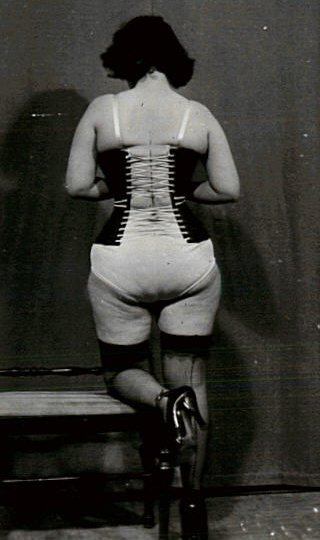 curvy woman lacing her corset