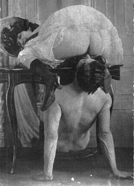 woman kneeling on a table with her pussy over a man\'s face