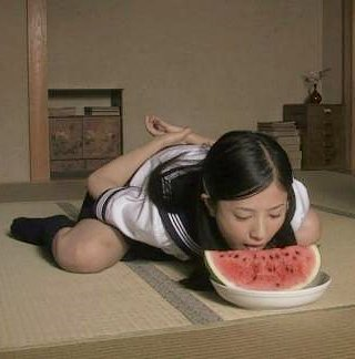 japanese girl eating a watermelon with her hands behind her back