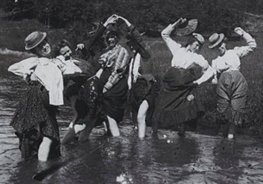 victorian women splashing in a cool stream with their skirts tucked up